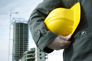 Man on building site holding hard hat